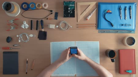 inventing : Top view software engineer is using cell phone smartphone on his desk full of equipment