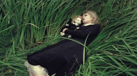 dead tree : Stylized shot creepy white faced woman with a doll in the grass in the woods laying Stock Footage