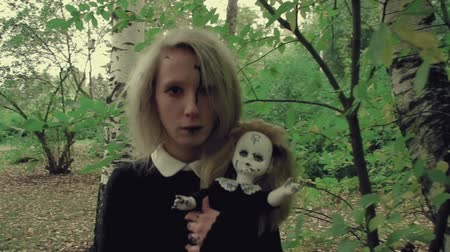possessed : Stylized shot creepy white faced woman with a doll in the grass in the woods