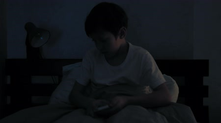 cobertor : Boy resting in his bed in the evening and using his smart phone and falls asleep Vídeos
