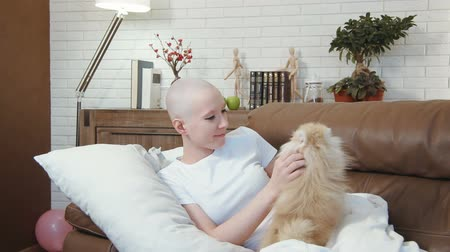 rak : Cancer patient woman lying on the sofa and playing with a little cute dog Wideo