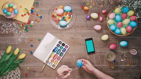 Man painting easter egg and smart phone with green screen lies on table decorated with easter eggs. Top view Stock mozgókép