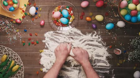 koszyk wielkanocny : Man kneading dough on table decorated with easter eggs. Top view