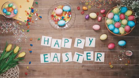 koszyk wielkanocny : Man put words Happy Easter on table decorated with easter eggs. Top view