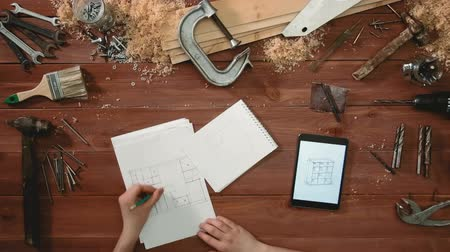 vállalkozó : Top view craftsman hands drawing a sketch of floor plan on paper using digital tablet