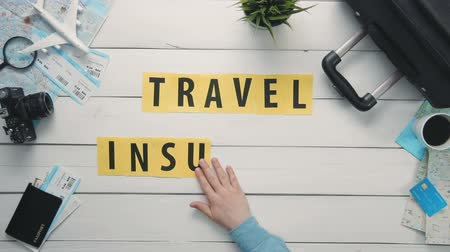política : Top view time lapse hands laying on white desk word TRAVEL INSURANCE decorated with travel items