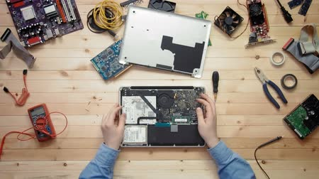 technikus : Top view computer technician opens broken laptop computer and repairs it at wooden desk with tools and electronic components