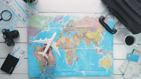 paper airplane : Top view travelers hand flying a toy airplane above the world map at white wooden desk Stock Footage