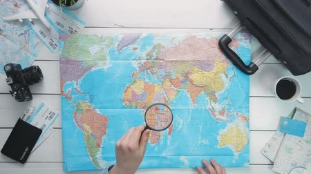 rajzszeg : Top view travelers hands looking at world map using magnifying glass at white wooden desk