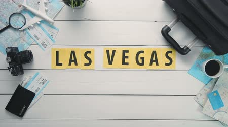 palavras : Top view time lapse hands laying on white desk word LAS VEGAS decorated with travel items
