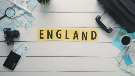 текст : Top view time lapse hands laying on white desk word ENGLAND decorated with travel items