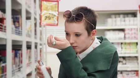 perfume bottle : Young woman choosing perfume in the supermarket, smelling bad perfume,