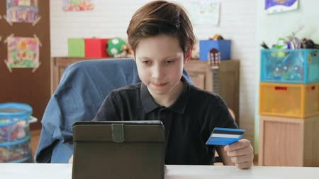ура : Cute little boy shopping online using entering credit card number using digital tablet and is happy after making a purchase Стоковые видеозаписи