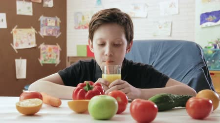 delicious : Cute little boy drinking orange juice with a straw on a table with healthy fruits and vegetables Stock Footage