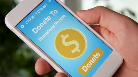 hobo : Man making an online donation to homeless people using charity applicaiton on smartphone Stock Footage