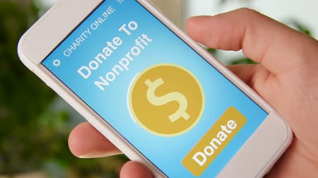 пожертвование : Man making an online donation to nonprofit organization using charity applicaiton on smartphone Стоковые видеозаписи