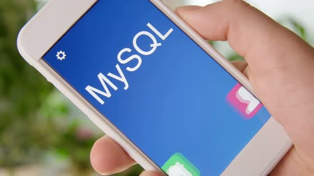 применения : MySQL concept application on the smartphone. Man uses mobile app. Стоковые видеозаписи