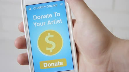 пожертвование : Man making an online donation to his favorive artist using charity applicaiton on smartphone