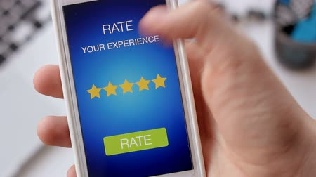 értékelés : Man gives five star rating using smartphone application Stock mozgókép