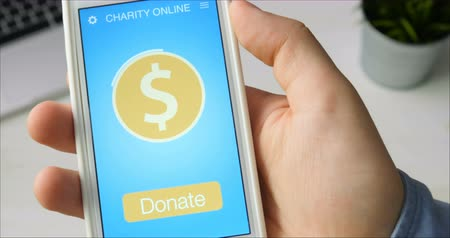 пожертвование : Man making an online donation using charity applicaiton on smartphone