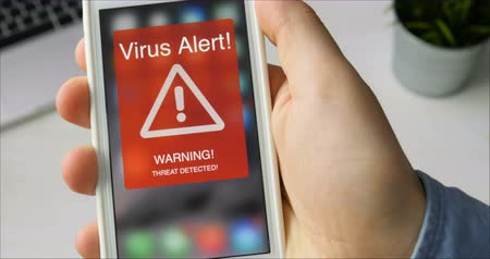 petya : Man holds smartphone with virus alert warning sign on the display