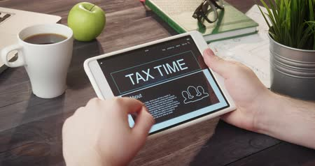 exemption : Checking tax time web page using digital tablet at desk