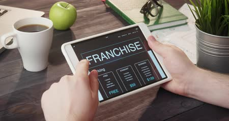 franczyza : Looking at franchise app using portable computer at desk