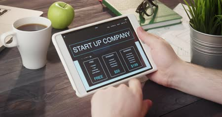 souprava : Browsing start up company landing page using tablet computer at desk