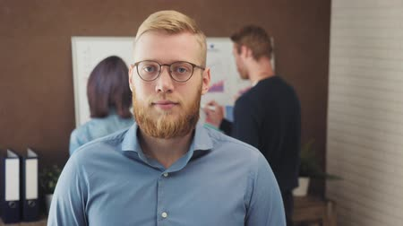 Portrait of a young businessman standing in a trendy office Stock mozgókép