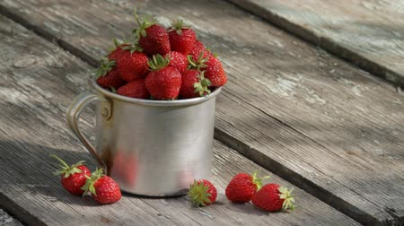 çilek :              Aluminium mug full of ripe strawberry, is on an old wooden table