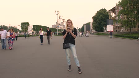 telefone celular : RUSSIA, MOSCOW - JULY 23, 2016: The beautiful blonde with iPhones leafing through photos in the park VDNKH Stock Footage