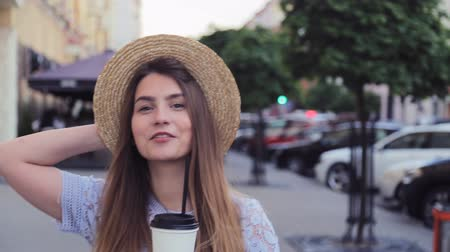 модный : Pretty girl in summer hat walking in the alley with take away paper cup