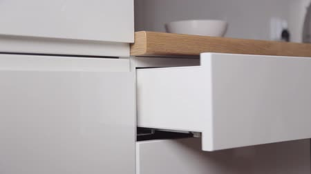 szekrény : The man takes the cutlery from the pull-out kitchen box with the push system