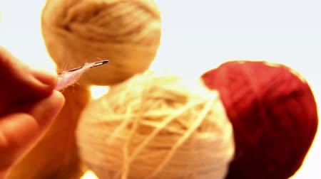 agulha : tangles of thread, a needle is inserted into a string and inserted into a ball