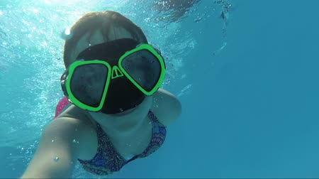 nadador : Happy girl in a mask under the water in the swimming pool looks into the camera, bubbles, sun rays Stock Footage