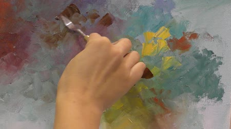 paleta : A painter paints a picture using a palette knife