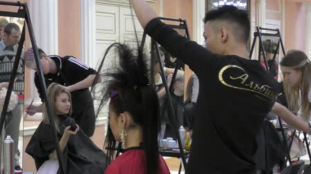 uzun : Orenburg, Russia - December 5, 2015: Hairdresser at the contest makes woman a hairstyle