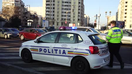 Editorial footage of a police car with the lights flashing in a junction in downtown Bucharest, Romania, 2020