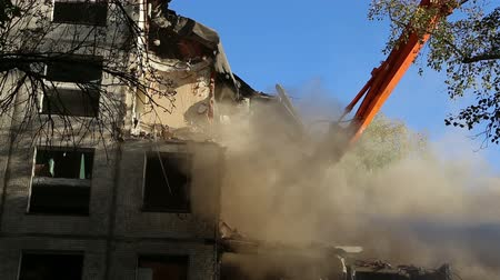 yıkım : Hydraulic crusher excavator machinery working on demolition old house. Moscow, Russia