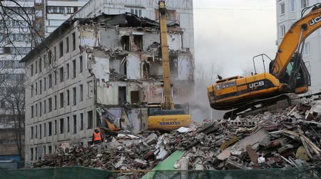 Excavator machinery working on demolition old house. Moscow, Russia