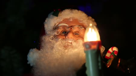 díszített : Santa Claus with a candle near the Christmas tree