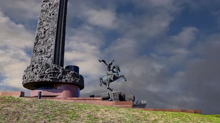 obelisk : Monument to Saint George slaying a dragon (on the background of moving clouds) on Poklonnaya hill in Victory Park, Moscow, Russia - memorial complex constructed in memory of those who died during the Great Patriotic war