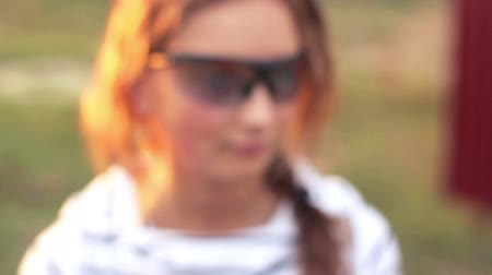 tehlike : Young beautiful girl in glasses with a gun shooting Stok Video