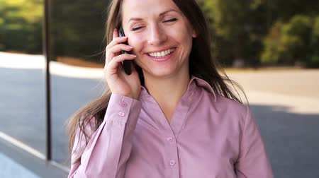 брюнет : Cheerful businesswoman talking on the phone Стоковые видеозаписи
