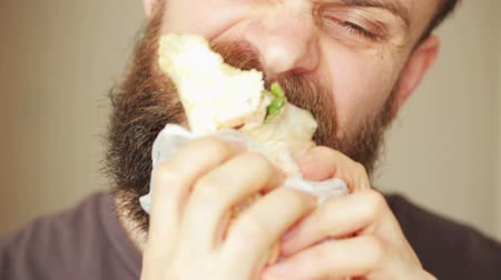 нездоровое питание : Bearded man eats kebab street food Стоковые видеозаписи