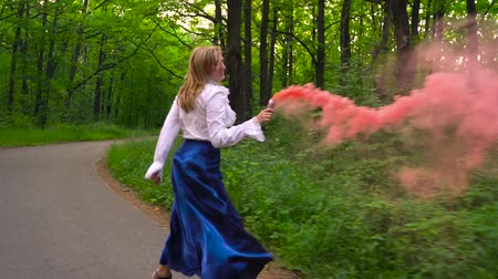 bomba : Woman in beautiful clothes runs through the forest waving colored smoke, slow motion Stock Footage