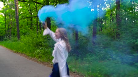 bomba : Woman in beautiful clothes runs through the forest waving colored smoke