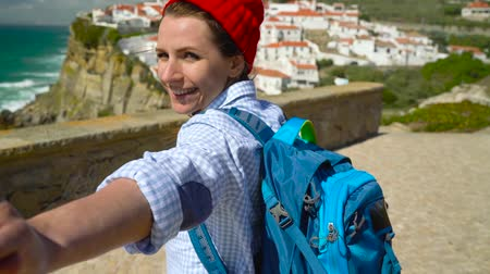 podróżnik : Follow me - happy young woman in a red hat and with a backpack behind her back pulling guys hand at Azenhas do Mar, Portugal. Hand in hand walking to the ocean coast Wideo