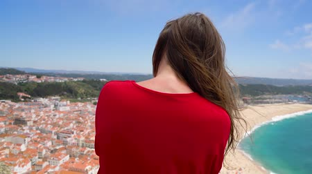 néző : Female tourist using coin paid binoculars on high hill and looking at cityscape of Nazareth, Portugal, slow motion Stock mozgókép