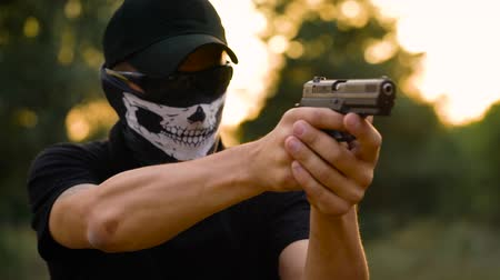 калибр : Man with the face closed with a handkerchief and sunglasses getting ready to shoot a gun, close up